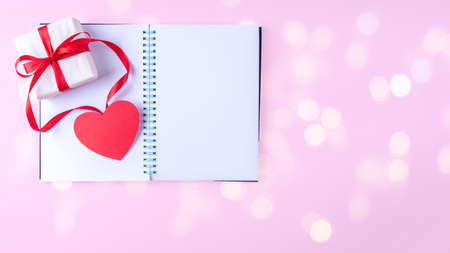 White blank open notepad, red pen, gift box with red ribbon and pink paper heart shape on pink background with bokeh, copy space, flat lay, top view, banner. Valentines day background