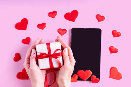 Online congratulations concept. Hands hold a gift with a red ribbon over a black blank tablet or phone screen with red heart shape on a pink background. Postcard for Valentines Day 版權商用圖片