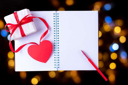 White blank open notebook, red pen, gift box with red ribbon and pink paper heart shape on black background with bokeh, copy space, flat lay, top view. Valentines day background 版權商用圖片