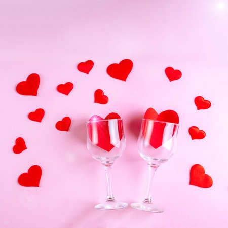 Happy Valentines Day greetings. Two wine glasses with red hearts on a pink background decorated with red heart shapes, flat lay, top view. Symbol of love, date, engagement