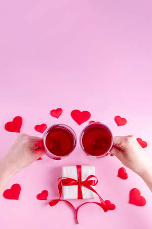 Happy Valentines Day greetings. Hands hold two wine glasses over a gift in white wrapping paper with a red ribbon on a pink background decorated with red heart shapes, top view, vertical frame.