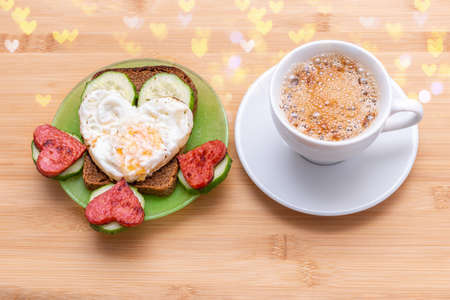 Coffee in a white cup and a sandwich with heart-shaped fried eggs, sausages and cucumbers on a green plate on a wooden background with bokeh, top view. Valentines Day Breakfast