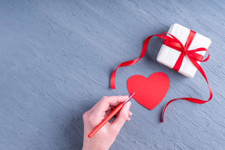 Happy Valentines Day greetings. Hand holds a red pen to sign a Valentine and a gift in white wrapping paper with red ribbon on gray trend 2021 background, top view, copy space