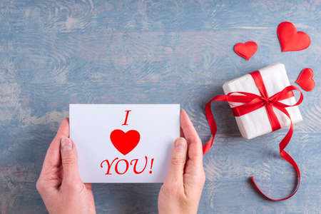Happy Valentines Day greetings. Female hands hold a love message, valentine card with the inscription I LOVE YOU next to a gift with red hearts on a wooden grunge blue background