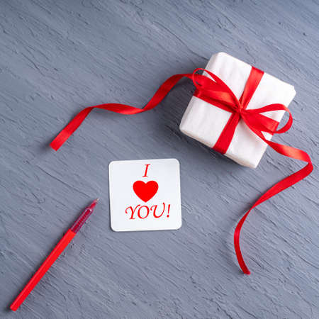 Stylish minimalist card with the inscription I love you. Gift in white paper with red ribbon, postcard and red pen on gray background. Can be used as a card for Valentines Day, Birthday, Fathers Day