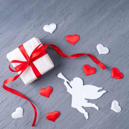 Gift in white paper with a red ribbon, an angel playing the trumpet, white and red heart shape on a stylish gray background, square shape. Can be used as a card for Valentines Day, Fathers Day 版權商用圖片