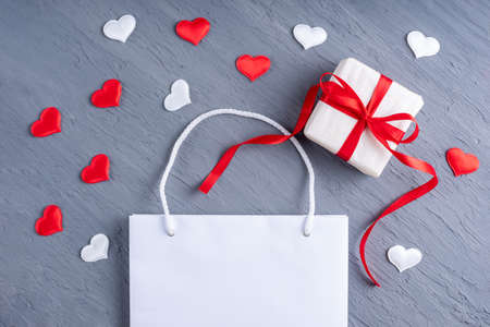 Online shopping concept. Bright white shopping bag and gift with red ribbon bows on trendy Ultimate gray background with red and white hearts. Valentines Day shopping and discounts concept 版權商用圖片