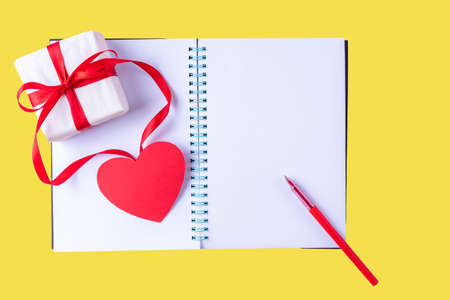 White blank open notebook, red pen, gift box with red ribbon and pink paper heart shape on yellow Illuminating 2021 background, copy space, flat lay, top view. Valentines day background 版權商用圖片
