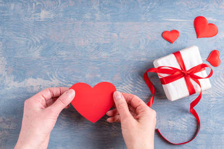 Hands hold a red heart shape next to a gift with a red ribbon bow and red hearts on a wooden grunge blue background. A symbol of love, relationships, dating, engagement. Valentines day concept 版權商用圖片