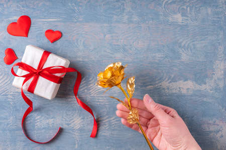 Female hand holds yellow gold rose and gift with red hearts on wooden grunge blue background, top view, copy space, selective focus. Symbol of love, relationship, dating, engagement