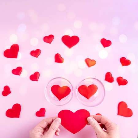 Hands hold a red heart shape, two glasses with hearts and white and red heart shapes on a pink background with bokeh, top view, copy space, square frame. Valentines Day concept 版權商用圖片