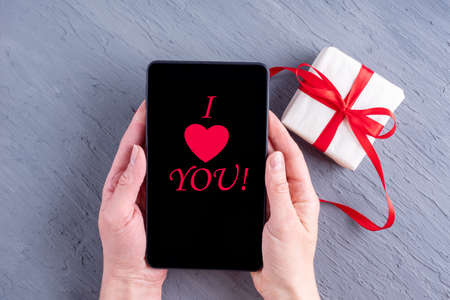 Online congratulations concept. Hands hold a tablet with the inscription I love you and a gift with a red ribbon on the Ultimate gray background. Card for Valentines Day, Fathers Day, Birthday