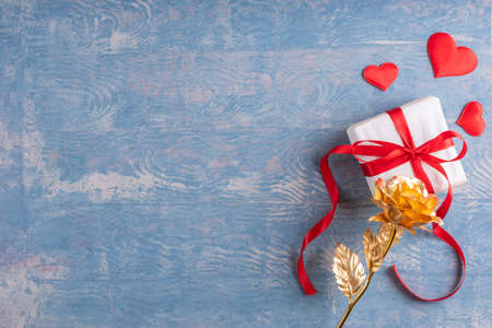 Happy Valentines Day greetings. Yellow gold rose, gift with red hearts on wooden grunge blue background, top view, copy space. Symbol of love, relationship, dating, engagement