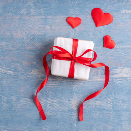 Gift wrapped in white paper with red ribbon and red heart shape on stylish wooden grunge blue background. Can be used as a card for Valentines Day, Birthday, Fathers Day 版權商用圖片