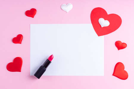White blank sheet, red lipstick and white and red heart shape on pink background, copy space, flat lay, top view. Valentines day background. Writing romantic letters, congratulations