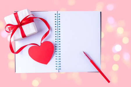 White blank open notebook, red pen, gift box with red ribbon and pink paper heart shape on delicate pink background with gold bokeh. Valentines day background. Writing romantic letters. 版權商用圖片