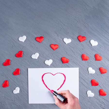 Love letter. Female hand draws a heart shape lipstick on white paper on a gray wooden background with white and red hearts, copy space, flat lay, top view. Valentines day background 版權商用圖片