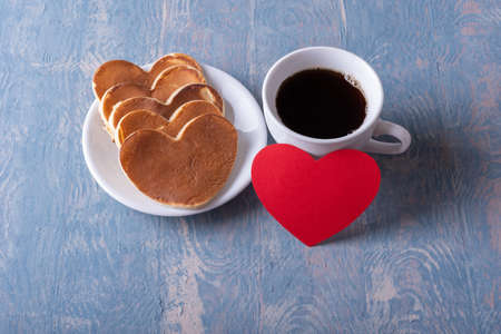 Homemade heart shaped pancakes on a white plate, a mug with coffee or cocoa and a red blank heart shape on a blue stylish wooden background, top view. Creative breakfast for Fathers Day. Love concept