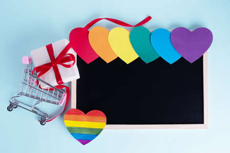 Gift box in shopping carts, multicolored rainbow colored paper hearts and a blank board with copy space on a light blue background. Seasonal sale, discounts, black friday concept. LGBT concept.