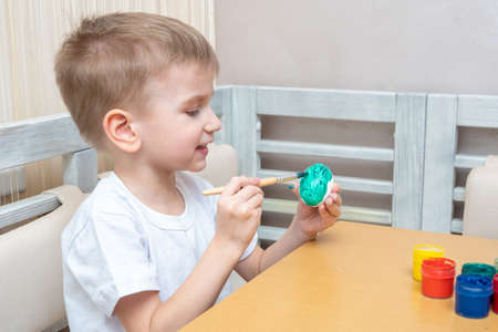 Easter eggs coloring concept. Happy caucasian boy sitting at the table and painting eggs for easter with green paint at home