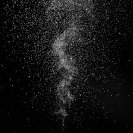 Curly white steam rising up and splashing water scattering in different directions isolated on a black background. Evaporation of liquid and condensation