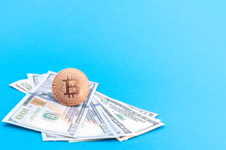 Bitcoin BTC virtual money on one hundred dollar paper banknotes on a blue background, copy space, close-up