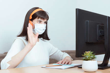 Charming brunette woman in orange headphones and a medical mask with a video call and a welcome gesture Foto de archivo