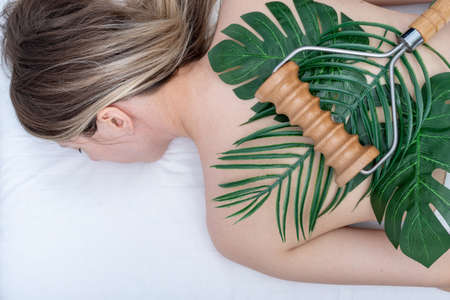 woman having spa back massage using a wooden roller massager lying on green leaves on her back. Body care