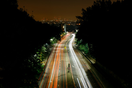 Aerial view of traffic light trails going into London, city skyline on the background.