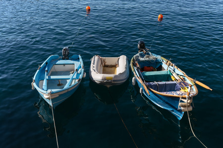 Three small fishing boats anchored and floating in a calm blue sea near the coast of Cinque Terre, Italy. Stock Photo