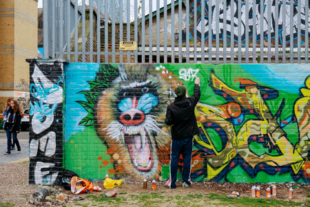 Artist finishing the graffiti on a wall in Shoreditch, area of London famous for street art.