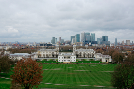 View of National Maritime Museum and London skyline from the top of the hill in Greenwich Park.