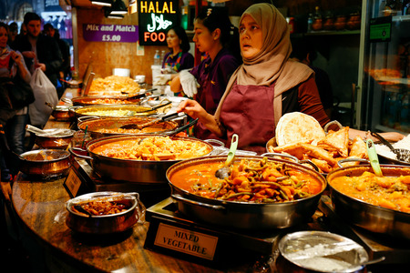 Traders at a market stall selling curry and varieties of cooked foods at Camden Market. Editorial