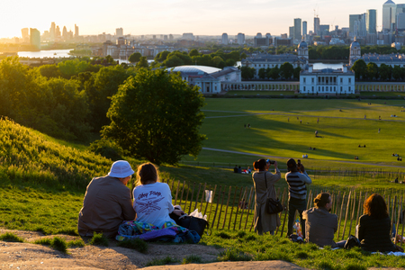 People on the top of the hill at Greenwich Park, watching the sunset and taking photos. Every year millions of Londoners and tourists visit Greenwich Park.