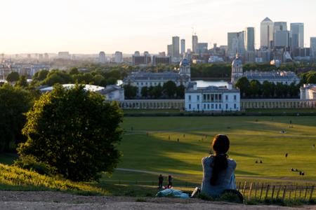 여자 그리니치 공원, 런던에서 언덕 꼭대기에 바닥에 앉아서 일몰을보고 스톡 콘텐츠