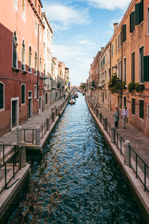 Couple walks alongside Venetian canal. Venice is an popular tourist destination for its uniqueness and celebrated art and architecture.