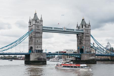 water bus: River cruise boat, tour bus and a plane next to Tower Bridge . Tower Bridge is often mistaken for London Bridge, the next bridge upstream.