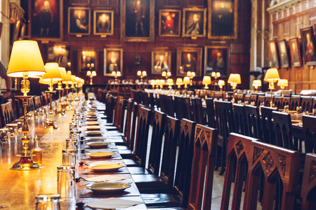 Tables set at The Great Hall of Christ Church, University of Oxford, England. The Hall was replicated at film studios as the dining hall at Harry Potters Hogwarts school.