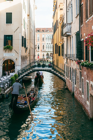 Gondolas on a narrow canal leading to Grand Canal in Venice. Gondola rides and tours are the citys iconic features and are very popular among tourists.