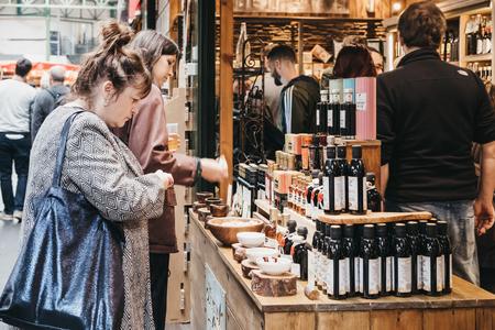 As mulheres experimentam azeite de oliva e vinagre em uma banca de mercado no Borough Market, um dos maiores e mais antigos mercados de alimentos de Londres. Editorial
