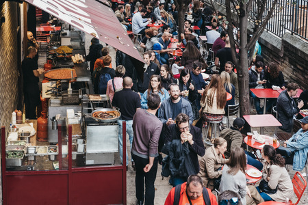 People walking past market stalls in Borough Market, one of the largest and oldest food markets in London.