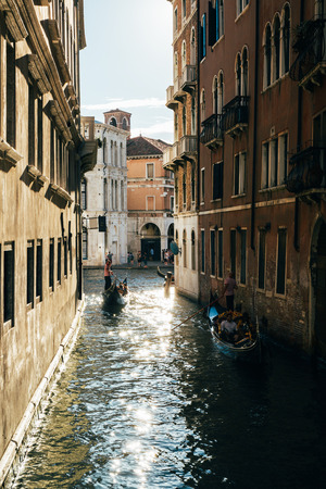 Gondolas on a narrow canal leading to Grand Canal in Venice. Boats are the main mode of transport in the city. Editorial