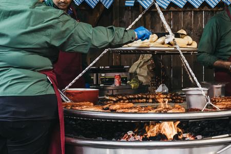 LONDON, UK - NOVEMBER 18, 2017: Staff cooking german sausages at Winter Wonderland, an annual Christmas fair in Hyde Park, London, UK Editorial