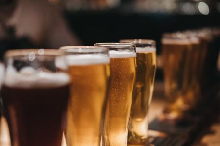 Primo piano di un rack di diversi tipi di birre, scuro alla luce, su un tavolo. Messa a fuoco selettiva.
