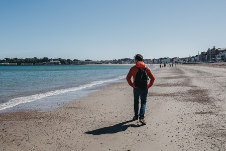 Young man in red jacket and jeans walking on Weymouth beach, Dorset, England on a clear sunny day.