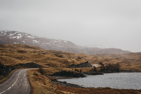 Road going through Scottish Highlands near Lochinver on a foggy spring day. Banque d'images