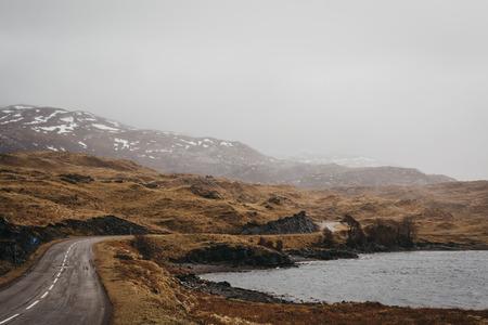 Road going through Scottish Highlands near Lochinver on a foggy spring day. Archivio Fotografico