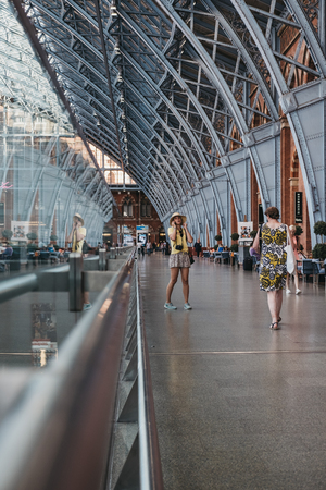 Woman in a yellow top talking on the phone inside St. Pancras Station. St. Pancras is one of the largest railway stations in London and a home to Eurostar. Editorial
