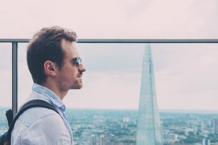 Side view of a man enjoying the view from an open air balcony in Sky Garden, London, Shard on the background. Sky Garden, the highest public garden in London.