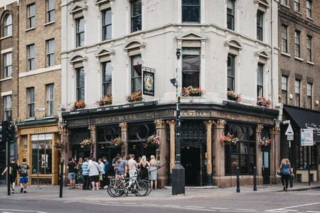 People standing and drinking outside The Ten Bells pub in Shoreditch, East London, pub famous for its supposed association with two victims of Jack the Ripper.